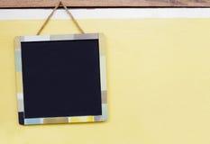 有垂悬在黄色混凝土墙上的多色框架的黑板 免版税库存图片