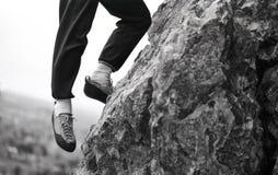 有垂悬峭壁露出边缘的一只脚的攀岩运动员在看下面谷 库存图片