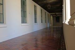 有垂悬的光的白色走廊 免版税库存照片