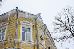 有垂悬从屋顶的冰柱的黄色房子 免版税库存照片