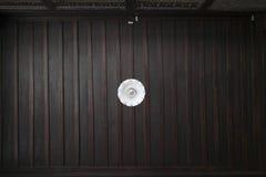 有垂悬从黑褐色天花板的白色护板的唯一灯 免版税库存照片