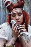 有垫铁和一只不可思议的鸠的巫婆在她的手上 库存图片