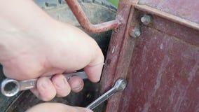 有垫铁钥匙的干净的手拉紧在一辆老生锈的独轮车的坚果 股票录像