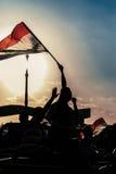 有埃及旗子的埃及活动家反对日落 免版税库存照片