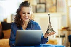 有埃菲尔铁塔纪念品的愉快的现代妇女使用膝上型计算机的 免版税库存照片