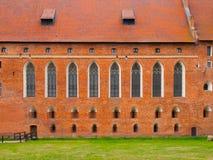 有城堡教堂高哥特式窗口的砖墙在马尔堡,波兰 免版税库存图片