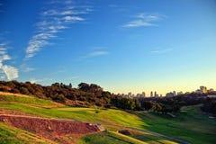 有城市地平线的高尔夫球场在距离 库存照片