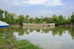 有城市的湖边钓鱼竿在背景中在晴朗的夏天af 免版税库存照片
