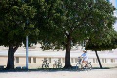 有城市自行车的少妇旅游骑自行车的人在海附近的镇 免版税库存照片