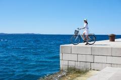 有城市自行车的年轻女人旅游骑自行车的人在海附近的镇 库存图片