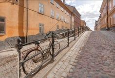 有城市自行车的街道被修补的石头停放了在五颜六色的历史房子之间 斯德哥尔摩,瑞典老地区  免版税库存图片