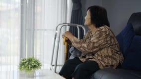 有基于和坐长沙发的藤茎的资深妇女 影视素材