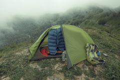 有基本的迁徙的齿轮的帐篷在Malabotta木头峰顶的云彩, 免版税图库摄影