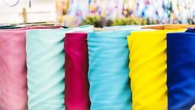有堆的传统织品商店五颜六色的纺织品,织品卷在市场上使-与弄脏的纺织工业背景失去作用 免版税库存图片