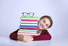 有堆的十几岁的女孩书在桌上坐白色背景 免版税库存图片