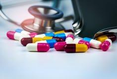 有堆的听诊器在白色桌上的五颜六色的抗药性胶囊药片与药物盘子 抗菌药物抗性 库存照片