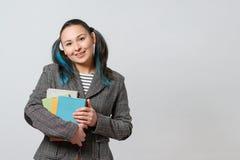 有堆的女生书在她的手上看照相机和微笑 特写镜头 免版税图库摄影