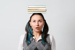 有堆的滑稽的女生在她的头的书 免版税库存照片
