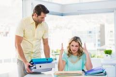 有堆的疲乏的创造性的女实业家在书桌上的文件 免版税库存图片