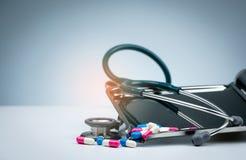 有堆的绿色听诊器在药物盘子的抗药性胶囊在白色桌上的药片和传播 抗菌药物抗性 免版税库存图片