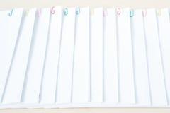 有堆超载文书工作的五颜六色的纸夹在木桌上 免版税库存照片