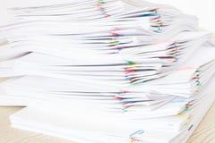 有堆超载纸的五颜六色的纸夹在木桌上 图库摄影