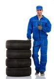 有堆车胎的年轻汽车修理师 免版税库存照片