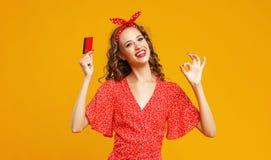 有塑料信用卡的美丽的滑稽的女孩购物的黄色颜色背景 库存照片