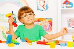 有塑料工具的聪明的男孩在教室 免版税库存照片
