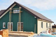有塑料房屋板壁和绝缘材料膜的修造的新房在议院外墙上 库存图片