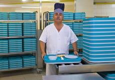 有塑料盘子的搬运工在医院厨房里 免版税图库摄影