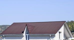 有塑料窗口和波纹状的板料一个棕色屋顶的议院  库存图片
