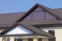有塑料窗口和波纹状的板料一个棕色屋顶的议院  免版税图库摄影