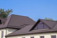有塑料窗口和波纹状的板料一个棕色屋顶的议院  库存照片