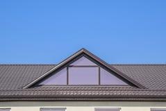 有塑料窗口和波纹状的板料一个棕色屋顶的议院  免版税库存图片