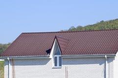有塑料窗口和波纹状的板料一个棕色屋顶的议院  免版税库存照片
