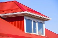 有塑料窗口和波纹状的板料一个红色屋顶的议院  图库摄影