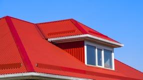 有塑料窗口和波纹状的板料一个红色屋顶的议院  库存图片