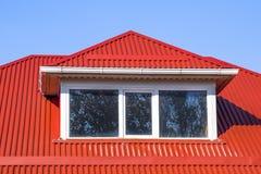 有塑料窗口和波纹状的板料一个红色屋顶的议院  免版税库存图片