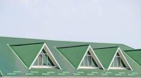 有塑料窗口和波纹状的板料一个绿色屋顶的房子  波纹状的金属外形和塑料窗口绿色屋顶  免版税库存照片