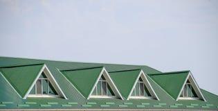 有塑料窗口和波纹状的板料一个绿色屋顶的房子  波纹状的金属外形和塑料窗口绿色屋顶  免版税库存图片