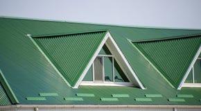 有塑料窗口和波纹状的板料一个绿色屋顶的房子  波纹状的金属外形和塑料窗口绿色屋顶  免版税图库摄影