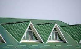 有塑料窗口和波纹状的板料一个绿色屋顶的房子  波纹状的金属外形和塑料窗口绿色屋顶  图库摄影