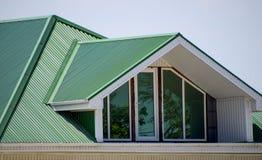 有塑料窗口和波纹状的板料一个绿色屋顶的房子  波纹状的金属外形和塑料窗口绿色屋顶  库存图片