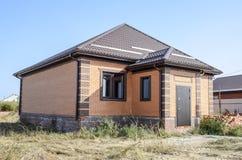 有塑料窗口和波纹状的板料屋顶的房子  免版税库存图片