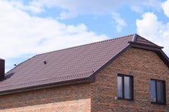 有塑料窗口和波纹状的板料屋顶的房子  免版税库存照片