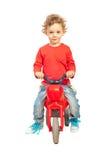 有塑料自行车的微笑的男孩 免版税库存图片
