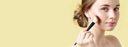 有塑造外形她的颧骨的雀斑的美丽的年轻红头发人妇女使用组成刷子 秀丽查出的纵向白色 免版税库存照片