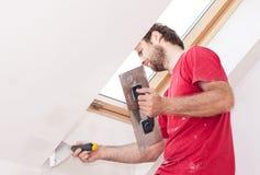 有墙壁的体力工人涂灰泥在房子里面的工具 免版税图库摄影