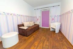 有墙纸的明亮的婴孩室 免版税库存图片